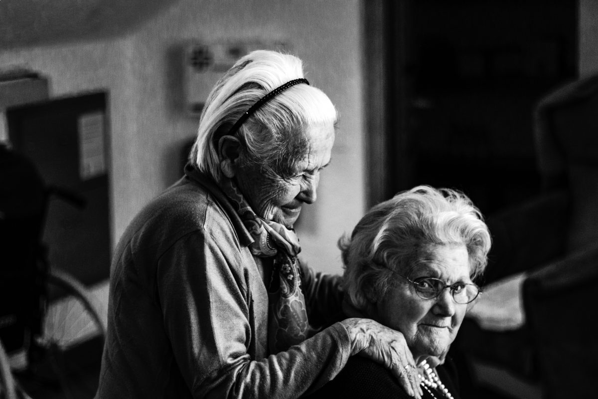 two old women standing near each other looking at the camera