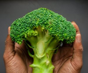 person holding broccoli in their hands