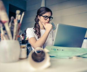 woman looking stressed while working at her computer