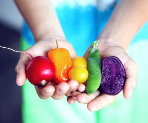 woman holding brightly colored vegetables