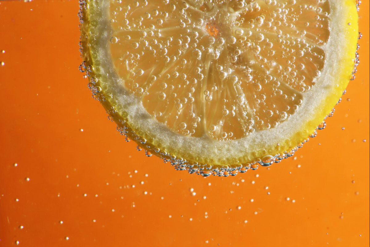 lemon slice in fizzy water with an orange background