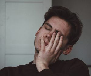 man looking tired with hand on his face