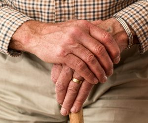 old man's hands resting on top of a walking cane