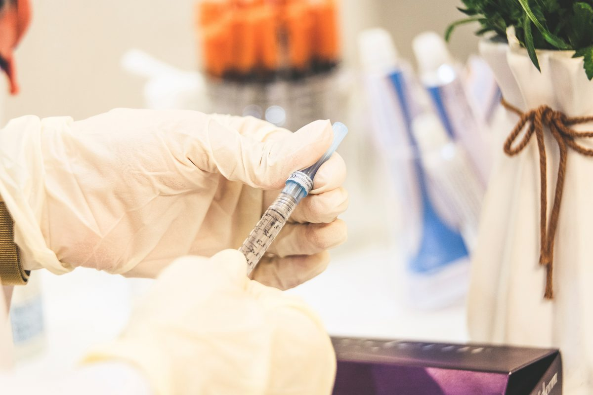 person in a medical lab filling a syringe