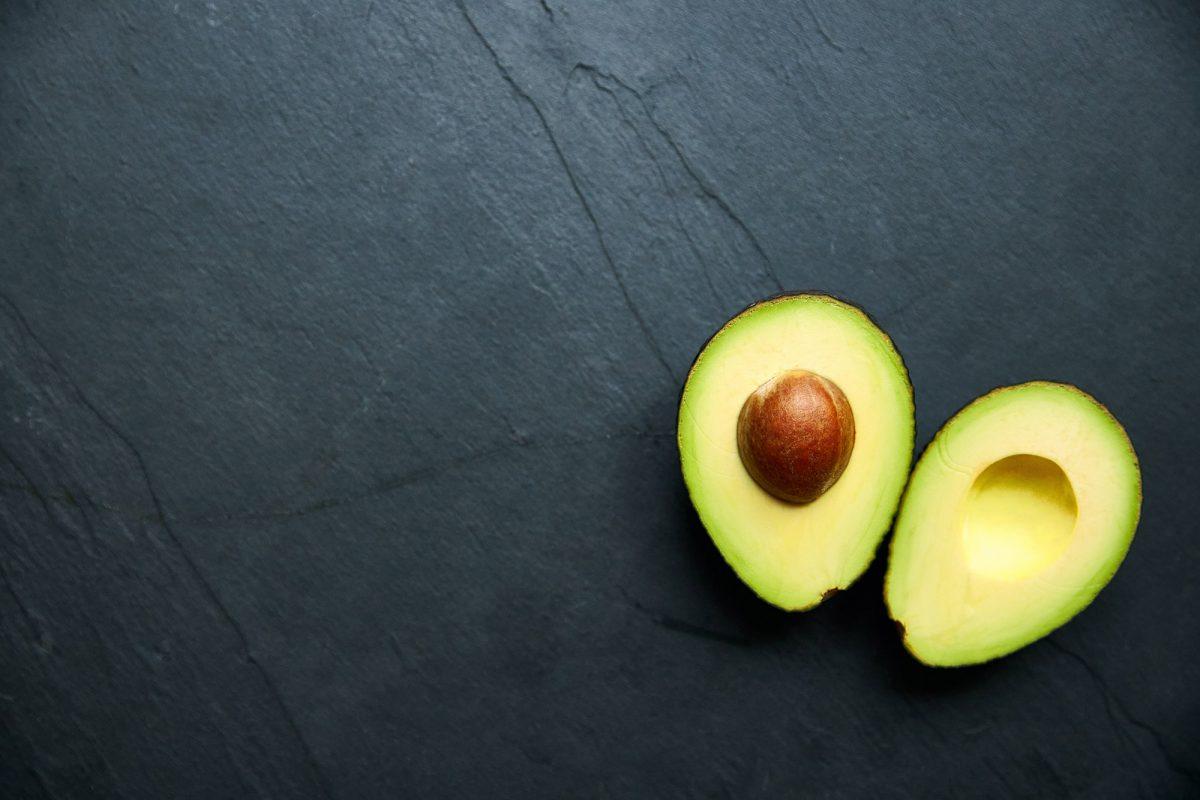 an avocado sliced in half against a black backdrop