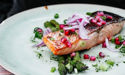 salmon fillet with vegetables on a white plate