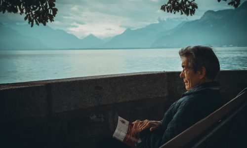 old man sitting on a bench overlooking a body of water