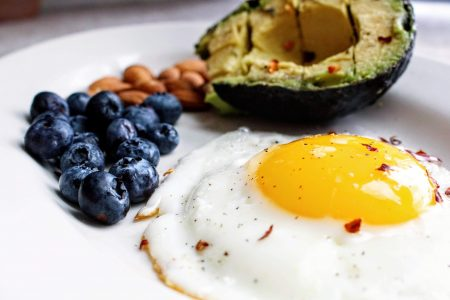 fried egg with blueberries and avocado and nuts on a white plate