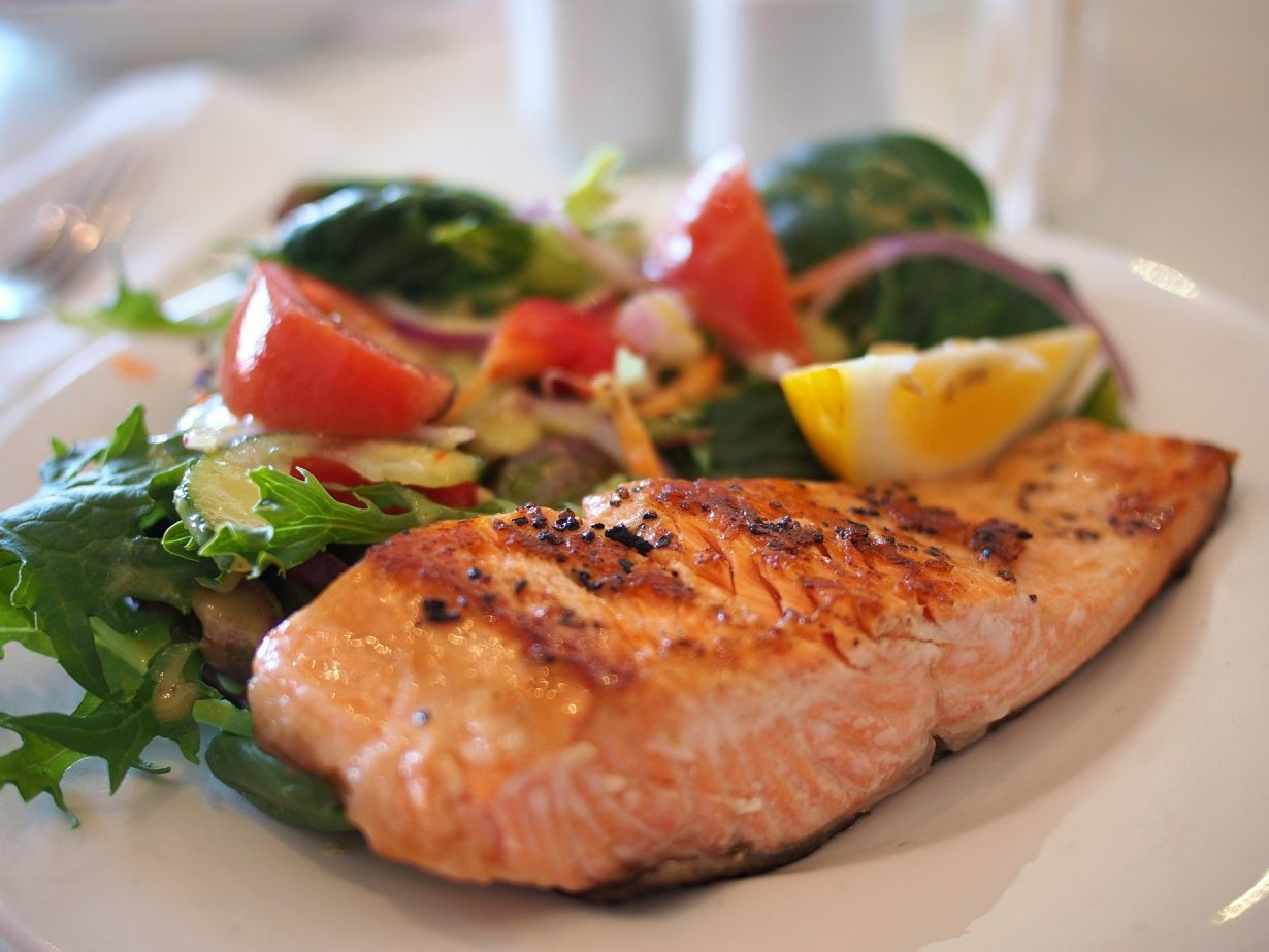 salmon fillet with side salad on white plate