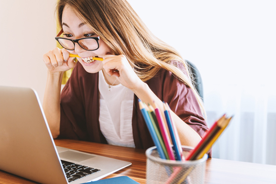 woman stressfully chewing on pencil