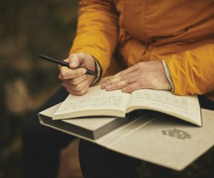 person holding a journal, pen and a book in their lap