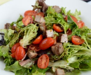 close up of a garden salad with meat and tomatoes