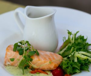 salmon fillet with green salad on a white plate