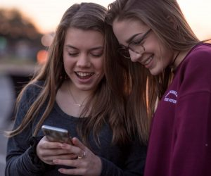 two teenage girls looking at a cell phone