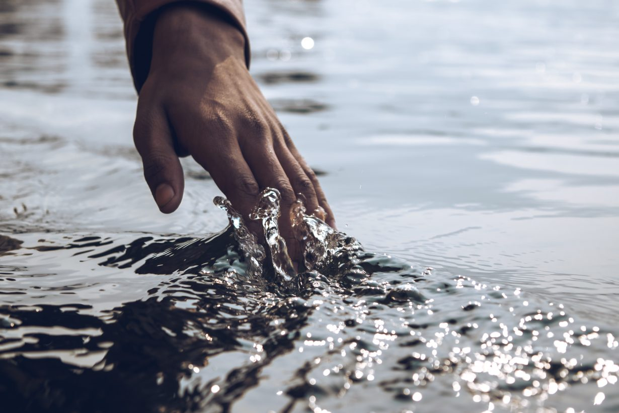 person running their hand over water