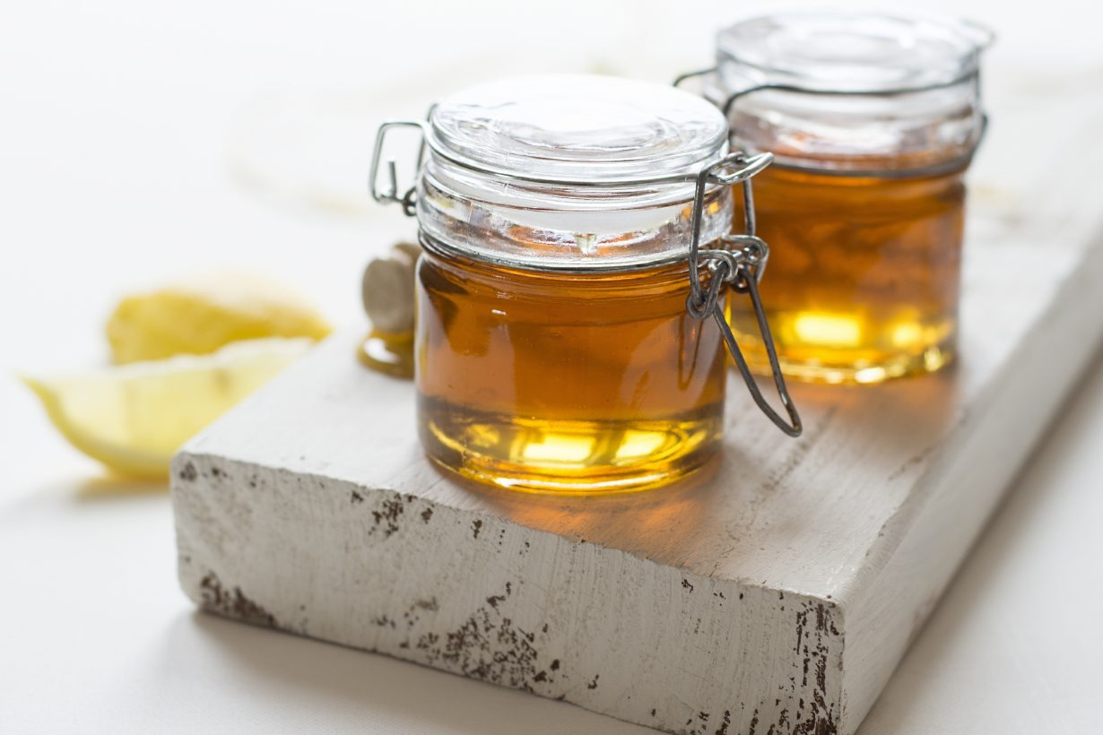 two jars of honey on a white plank