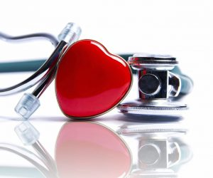 red heart leaning against a stethoscope