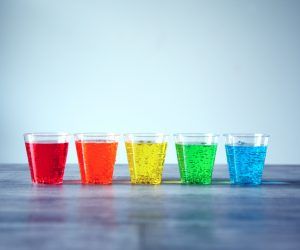 5 glasses lined up with rainbow colored fizzy drinks