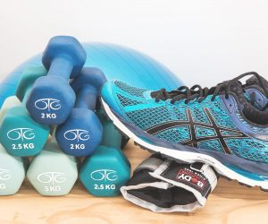 dumbbells stacked on a floor with a tennis shoe resting on them