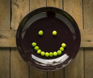 black plate with a smiley face made of peas