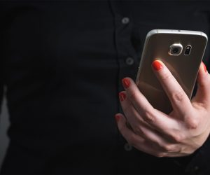 woman in a black shirt holding a smart phone
