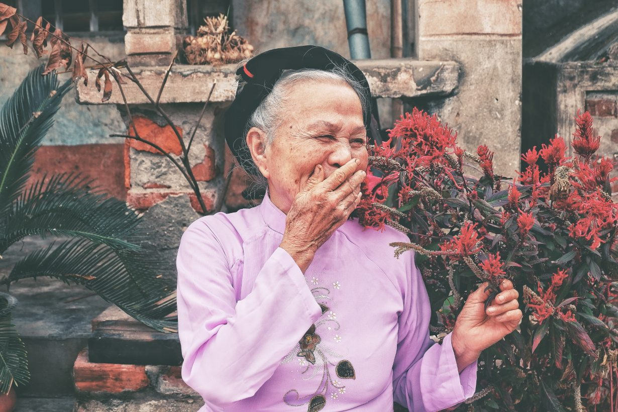 old woman laughing with her hand over her mouth