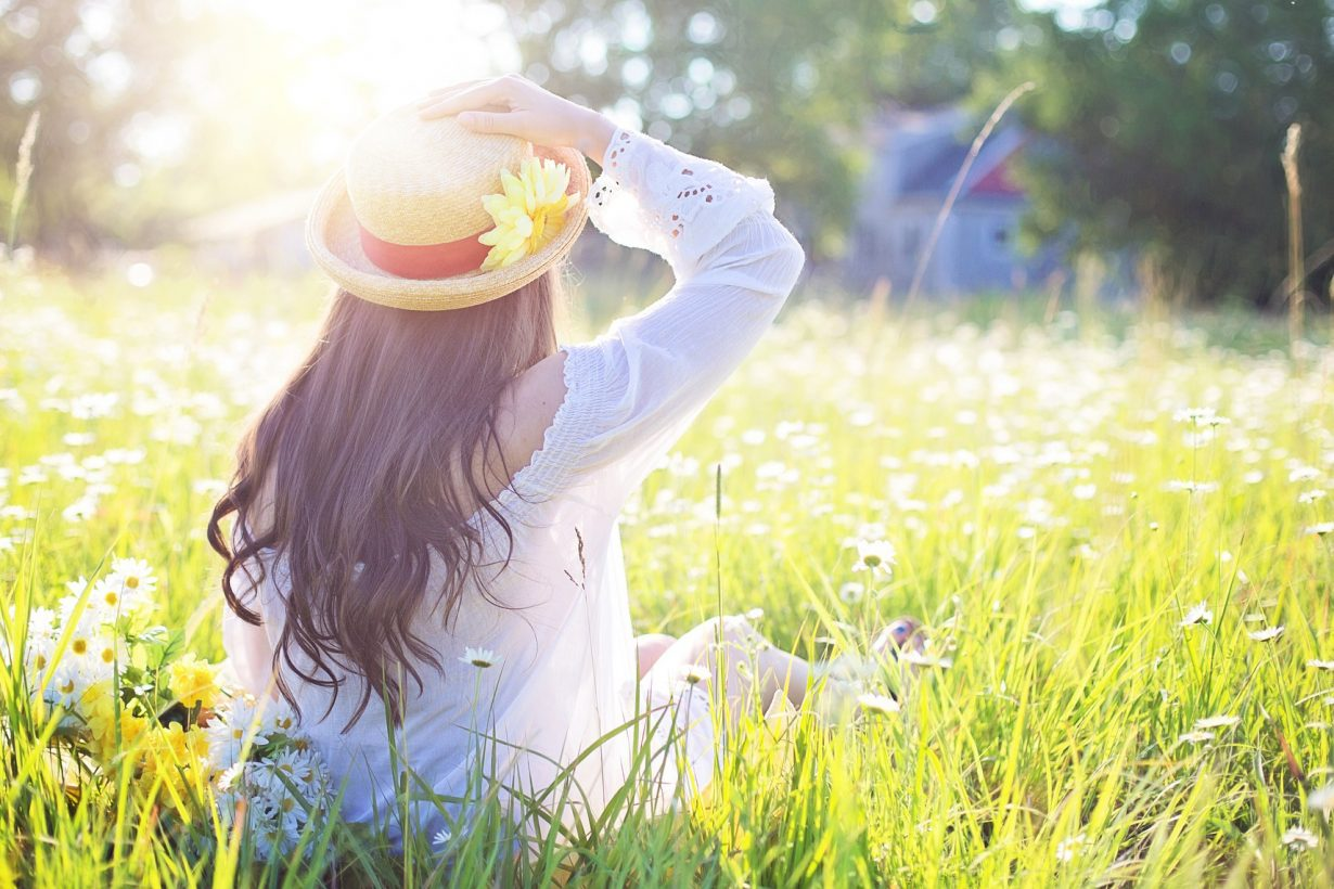 woman sitting in the grass with the sun shining on her