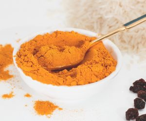 turmeric powder in a white bowl with a silver spoon