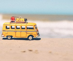 tiny bus on the sand in front of the ocean
