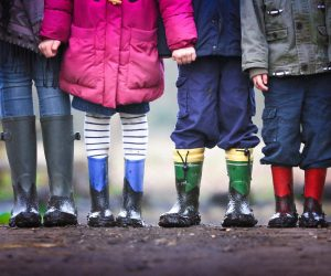 image of the legs of 4 children wearing rain boots