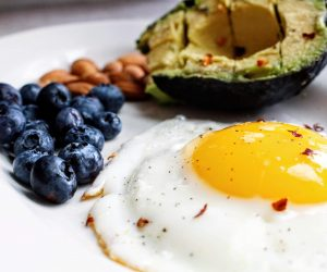 friend egg, blueberries, almonds and and avocado on a white plate