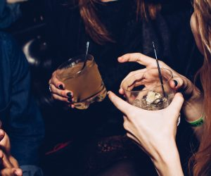 two people holding mixed drinks in their hands