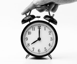 black and white photo of hand pushing a bell alarm clock