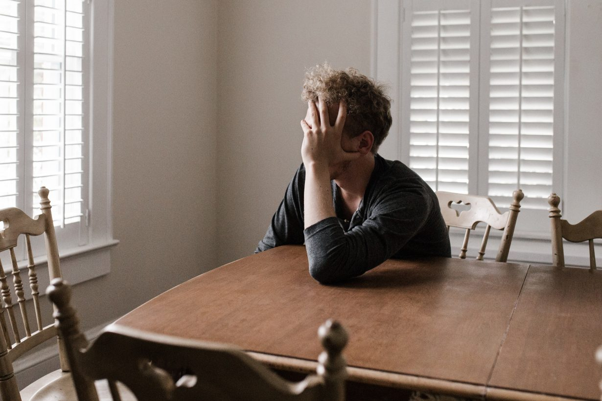 tired man leaning his head in his hands on a table