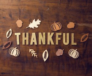 """""""Thankful"""" spelled out in letters on a table with leaves around it"""