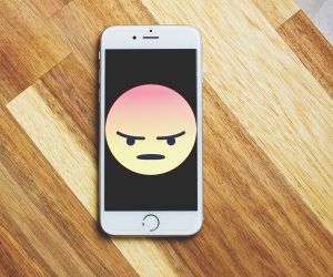 angry face displayed on a cell phone