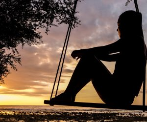 silhouette of a woman sitting on a swing