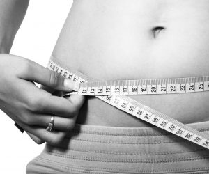 woman measuring her belly with a measuring tape