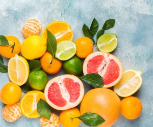 a punch of citrus fruits piled up on a blue background