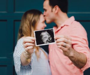 two people kissing holding their ultrasound picture