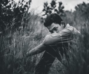 photo in black and white of a young man sitting in high grass looking sad
