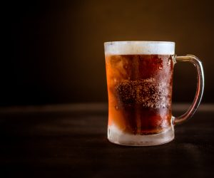 dark beer in a glass stein against a black backdrop