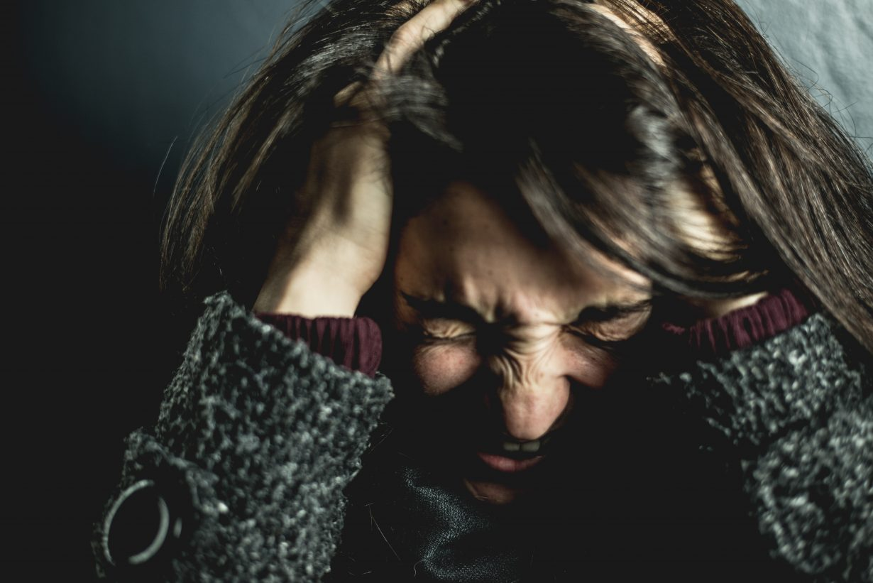 woman gripping her head in pain