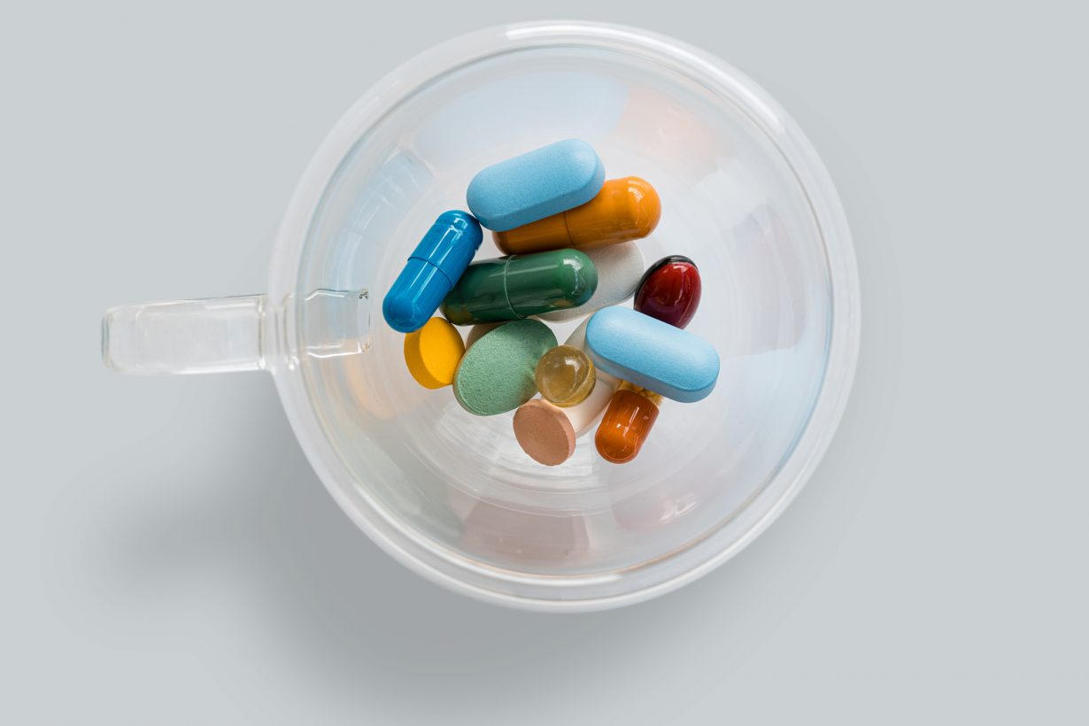 cup full of a bunch of medications