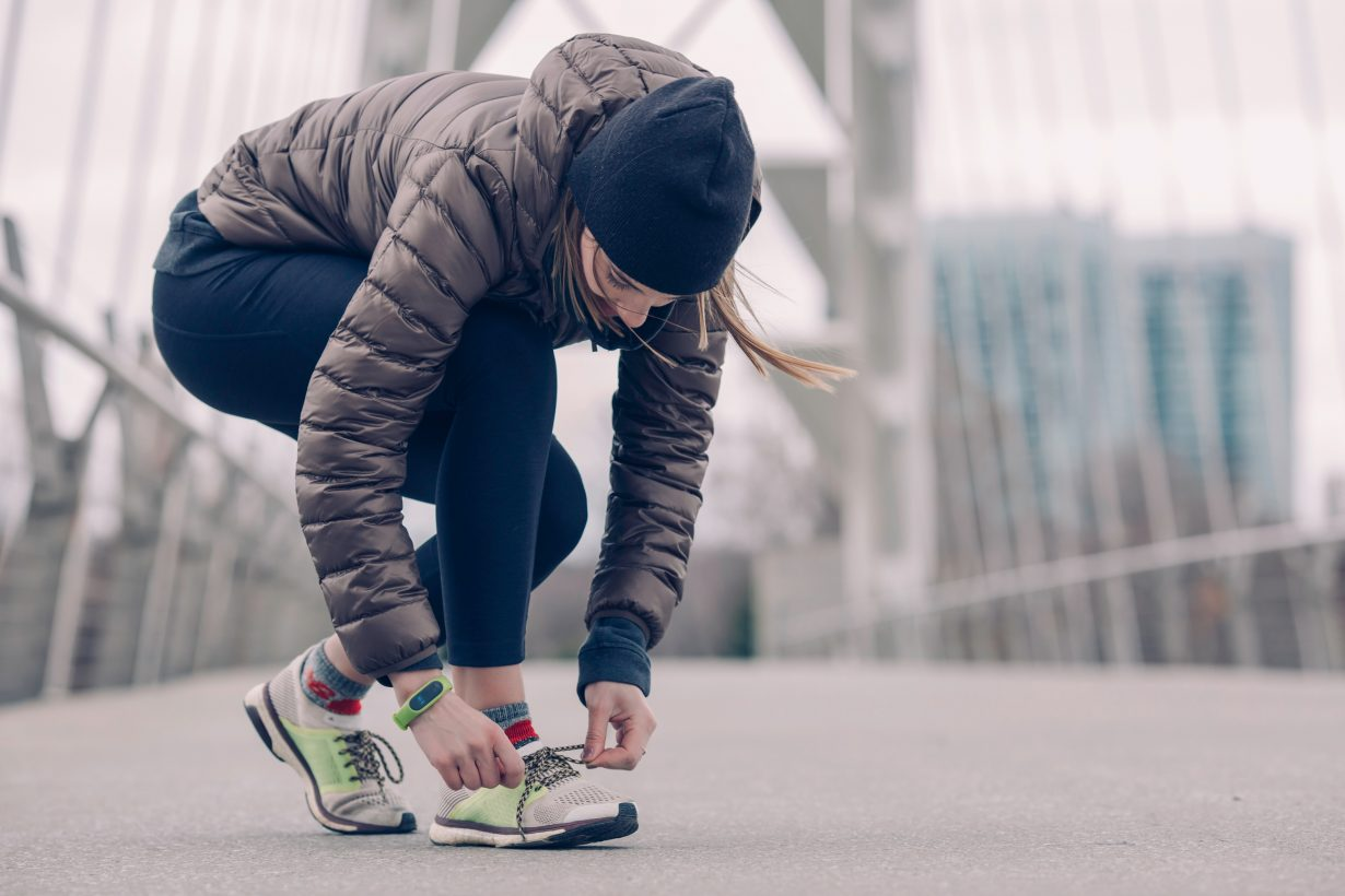 woman in workout clothes tying her shoe