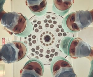 surgeons standing in a circle looking down at the camera