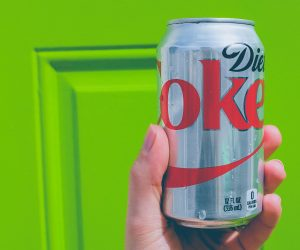 person holding a diet coke can against a bright green background