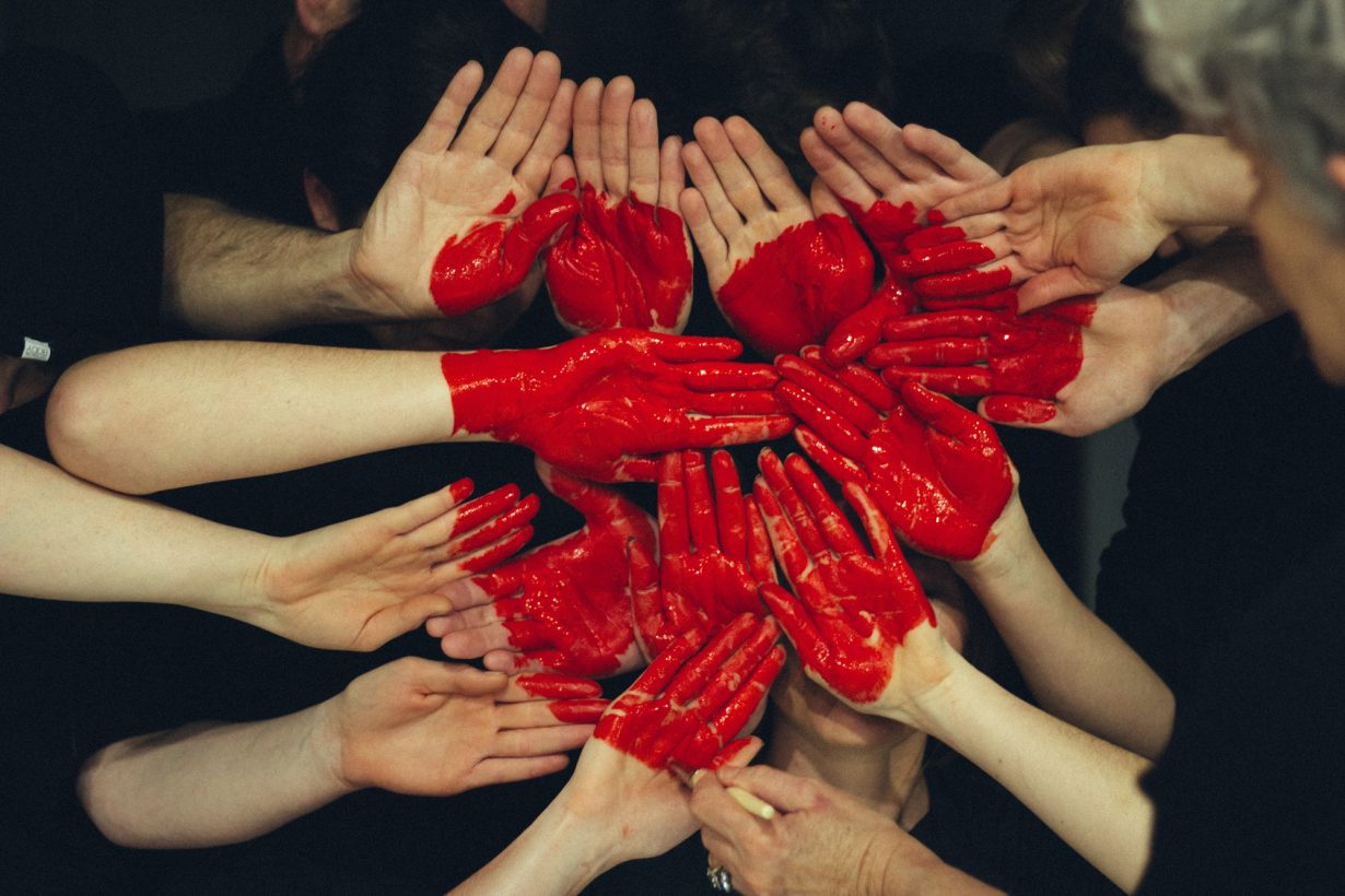 a bunch of hands painted read put together to make a heart