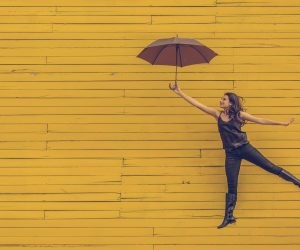 woman floating against a yellow wall with an umbrella