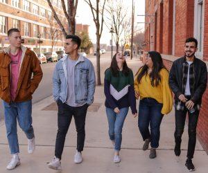 group of teenagers walking on a sidewalk